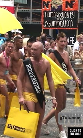 Gay men in speedos with shopping bags oblivious to fascists behind them