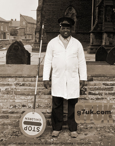 School crossing attendant takes a break in front of St.John's church, Longsight, probably 1985