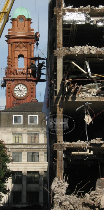 Workmen in a cage suspended from a crane inspect the front of the former BBC building during demolition