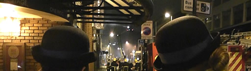 Two police officers look on as fire fighters tackle the blaze in Oldham Street